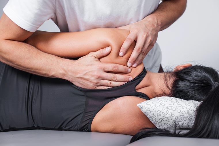Massage von Schulterblatt bei Frau